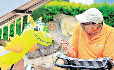 Ein Klappstuhl auf Reisen - HAZ Reporter Peter Rütters hat im Freibad Garmissen den Dino per Mund-zu-Mund-Beatmung wiederbelebt. Doch das Schwimmspielzeug macht beim Interview keine weiteren Angaben zur Person. Foto (c) Kaiser / HAZ