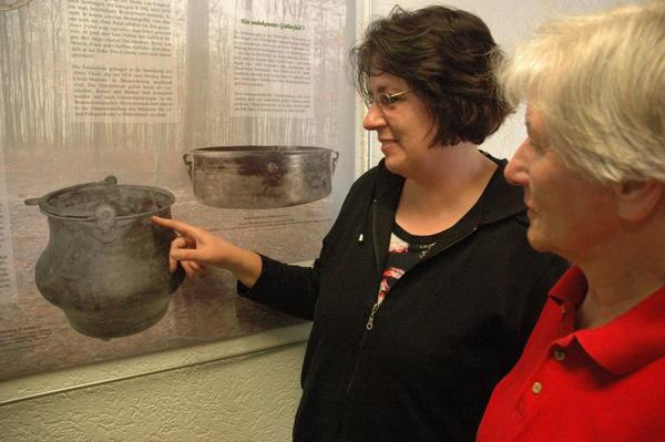 Die Schellerter Heimatpflegerinnen Heike Klapprott und Gerda Mayer erläutern die Fundgeschichte zu einem Römischen Kupferkessel, der im 19. Jahrhundert zwischen Wöhle und Nettlingen entdeckt wurde. Foto: Mierzowsky
